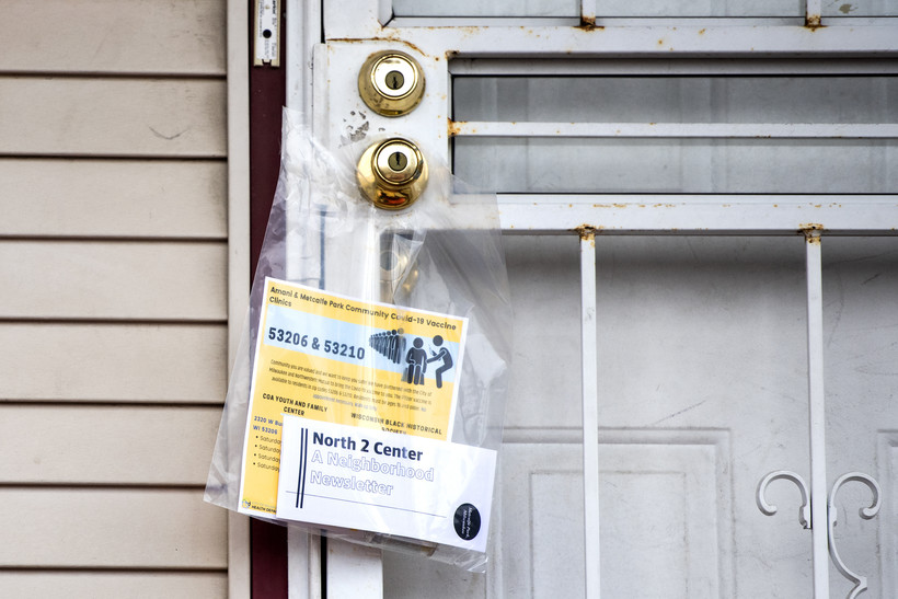 A plastic bag containing informational paperwork hangs on a doorknob.