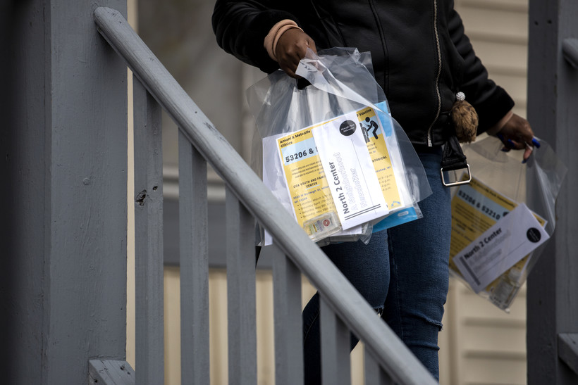 Plastic bags are carried by someone walking down a set of front porch stairs.