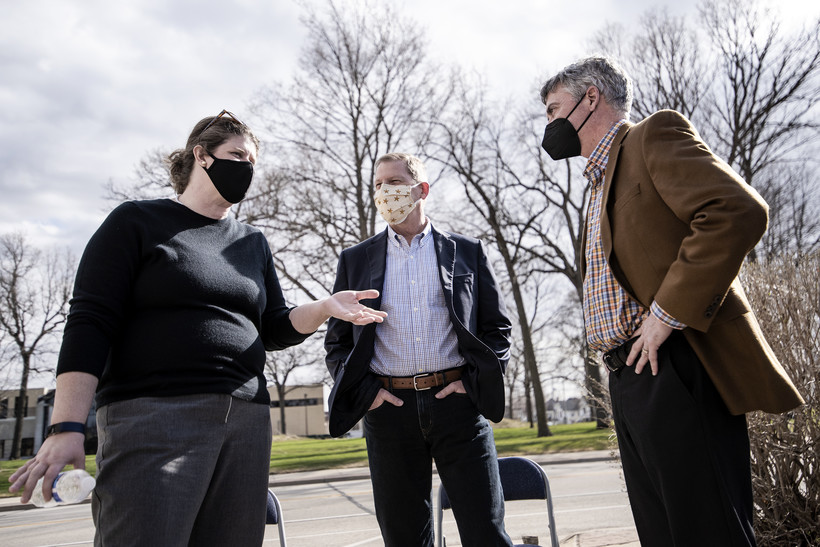 Three people wear face masks while speaking outside.