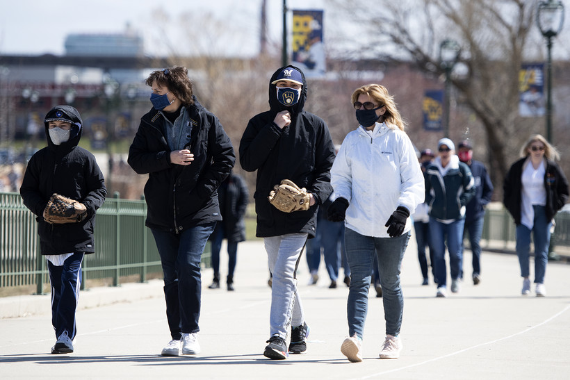 Fans wear face masks and hold baseball gloves as they walk toward the stadium.