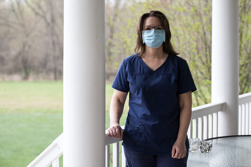 A nurse stands on a porch in scrubs and a face mask.