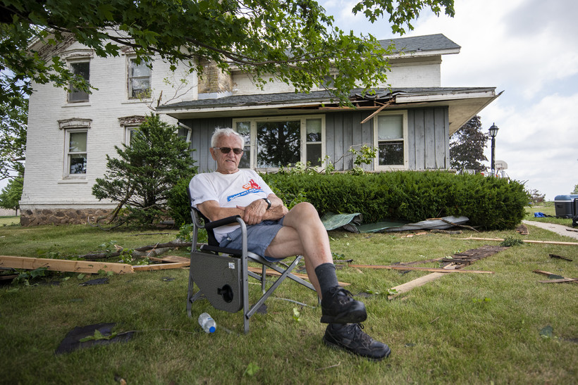 A man in sunglasses sits in a lawn chair in front of his home.