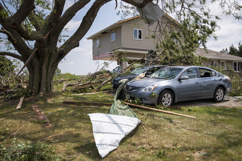 Two damaged vehicles sit next to a home with severe storm damage.