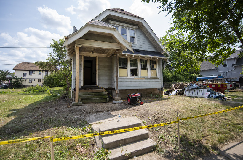 A blue home is mid-renovation. Yellow caution tape blocks off the front yard.