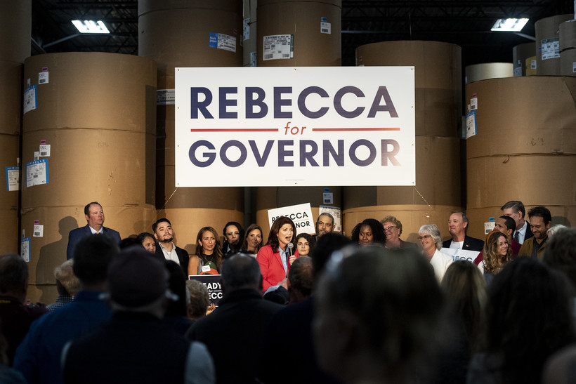 """A large white sign says """"Rebecca for Governor"""" behind the stage where Rebecca Kleefisch is speaking."""