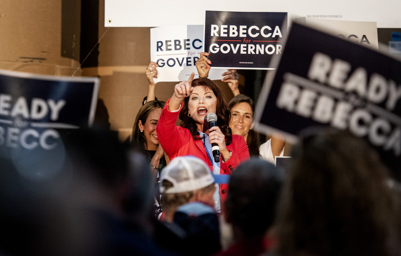People in the crowd hold up campaign signs as Rebecca Kleefisch points to them while speaking into a microphone.