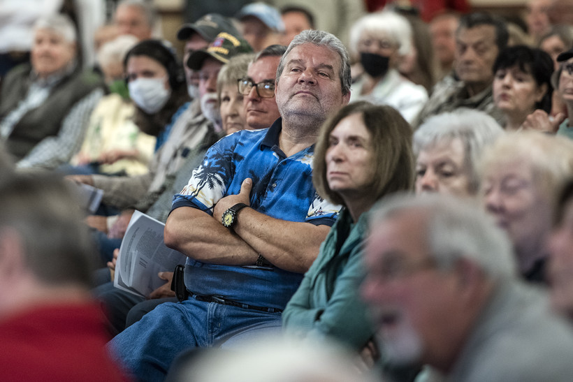 A constituent crosses his arms and lifts his head to see Sen. Ron Johnson.