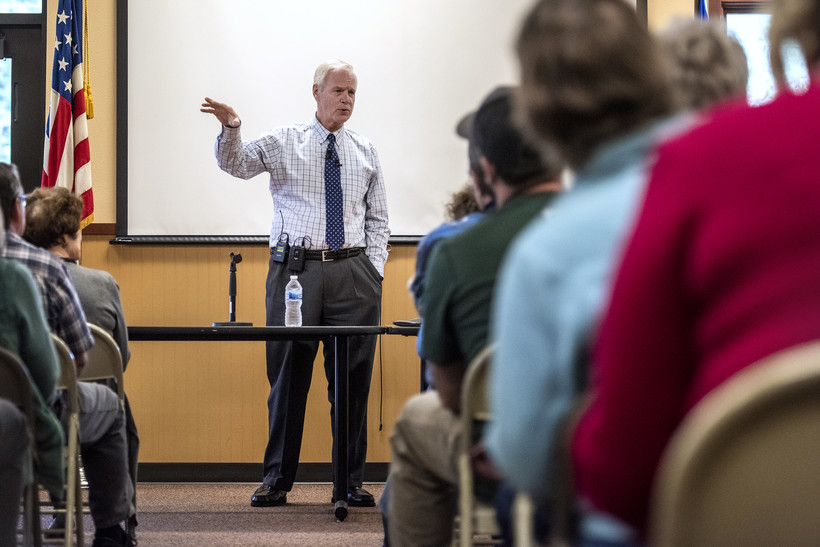 Sen. Ron Johnson gestures as he stands in front of a crowd of constituents.