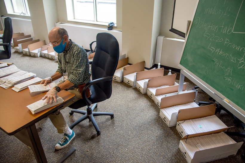 Election official Lenny Black alphabetizes returned absentee ballots in the City-County Building in Madison