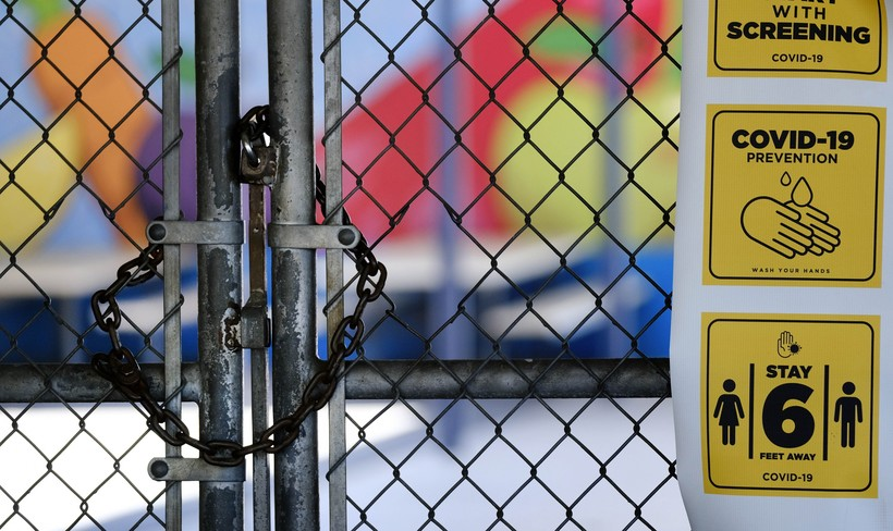 a chain-link fence lock is seen on a gate at a closed elementary school