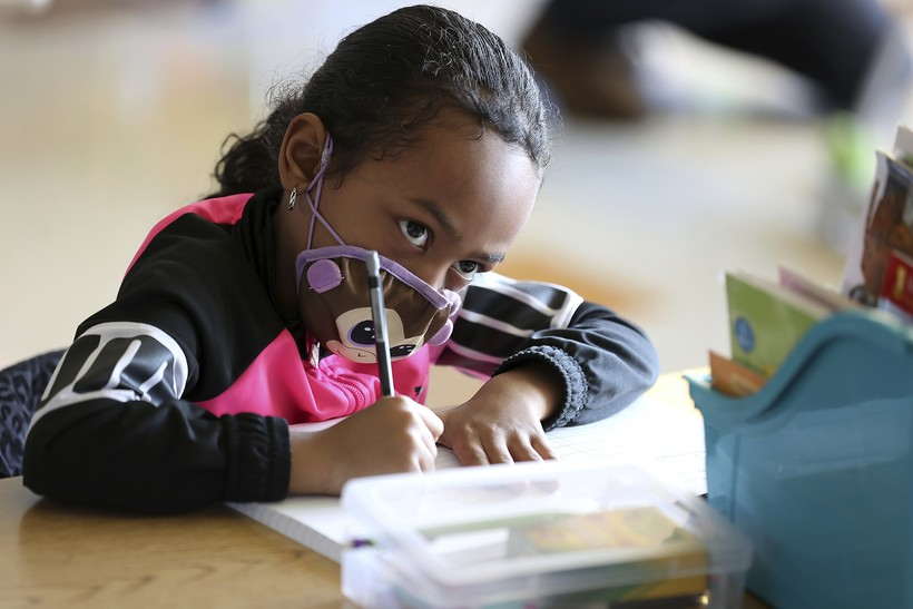 Cali Greenwood, a first-grader wearing a mask, looks up at her teacher