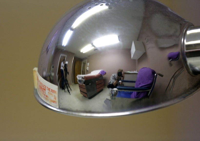 media are reflected in a lamp as they photograph a room formally used as an examination room for abortions