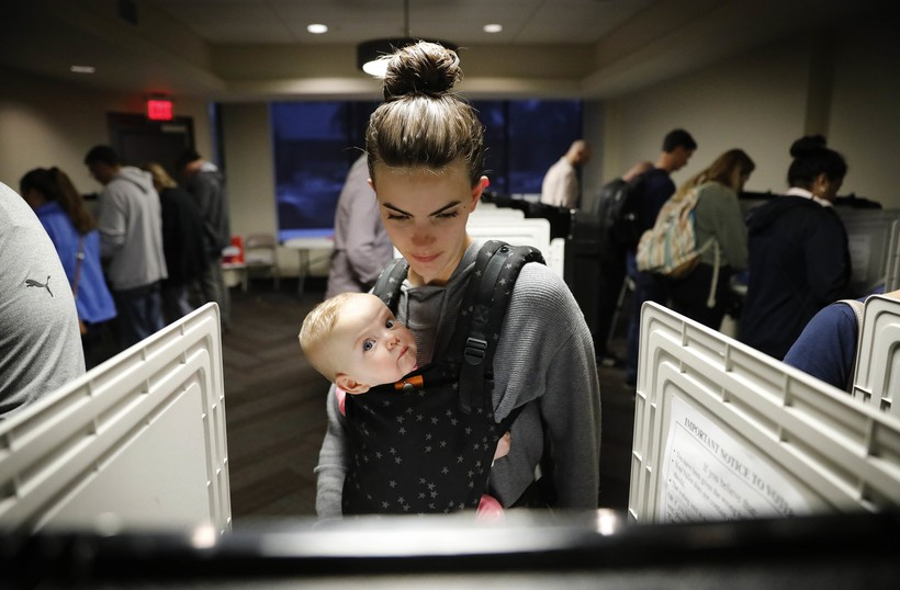 Kristen Leach votes with her six-month-old daughter,