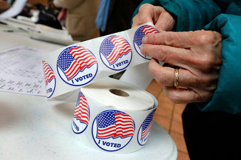 "A voter retrieves her ""I Voted"" sticker"