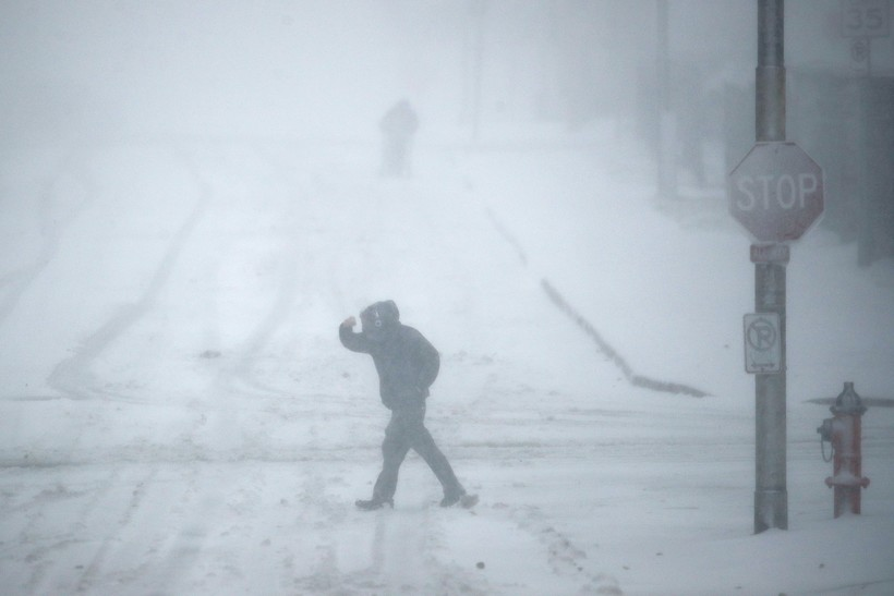 Pedestrians walk as snow falls