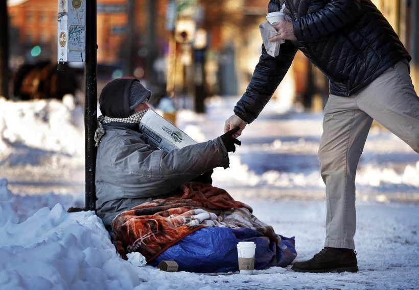A homeless man sitting outside a coffee shop accepts cash from a customer on a bitter cold morning