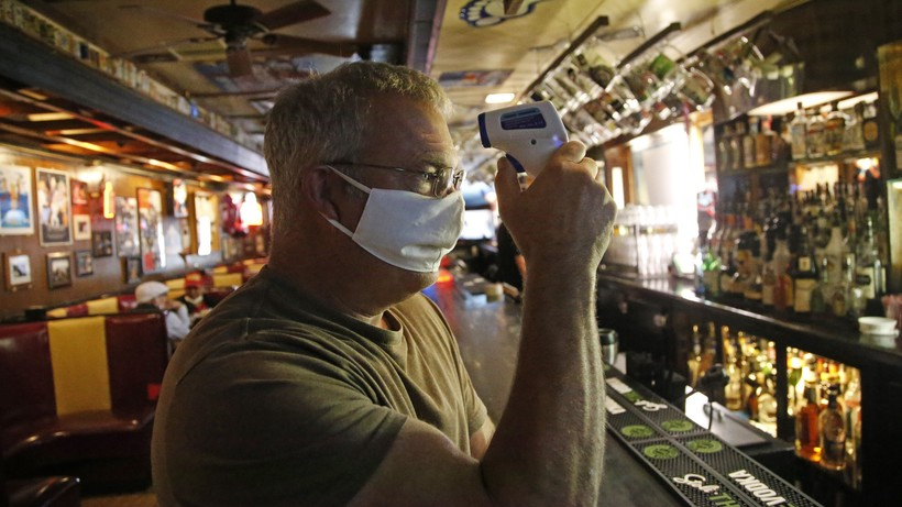 Cheers to You bar owner Bob Brown tests a thermometer at his bar