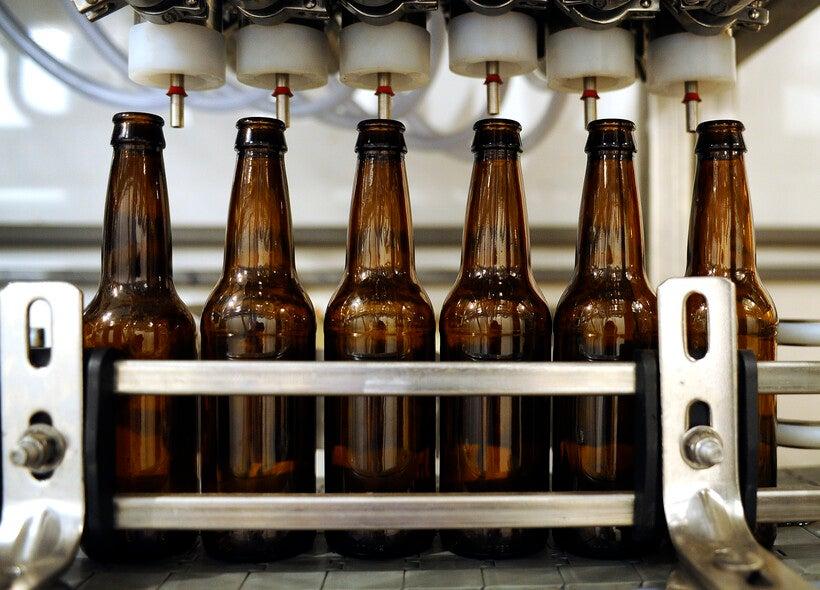 Beer bottles are lined up on a bottling line machine