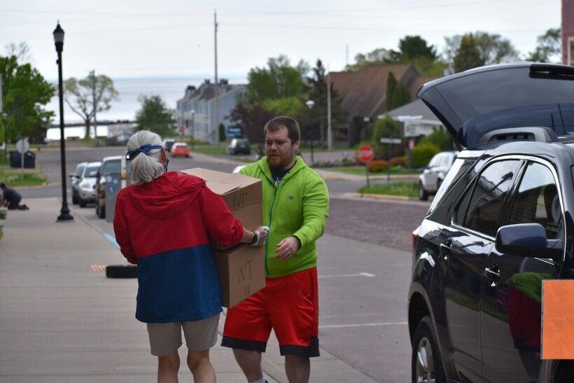 Volunteer Lisa Luttinen helps bring food boxes to Charles DeFoe