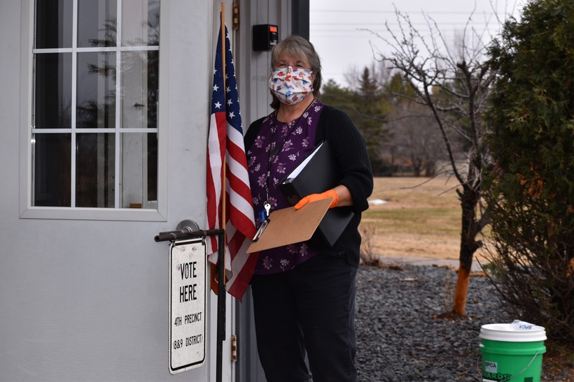 Kathy Izzard, donning a mask and gloves, has been helping people vote