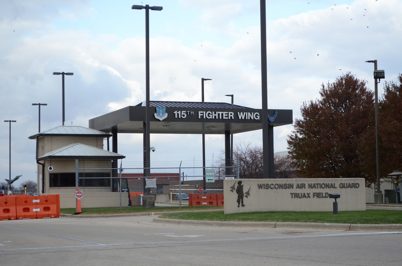 A sign for the Truax Field Air National Guard Base stands before a larger sign for the 115th Fighter Wing.