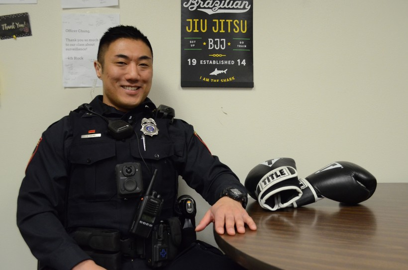 A man in full police uniform sits smiling at a table next to a pair of boxing gloves.