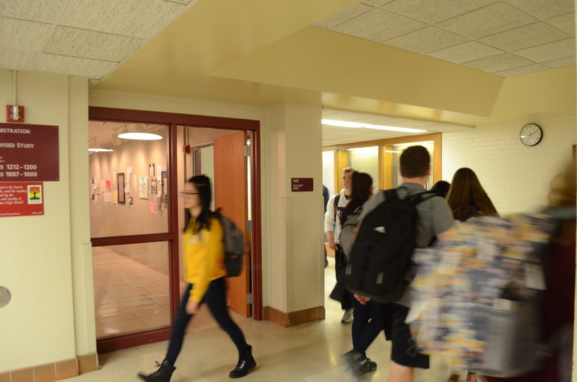 Students carrying backpacks, blurred with motion, walk through the red-and-white hallways of Middleton High School.