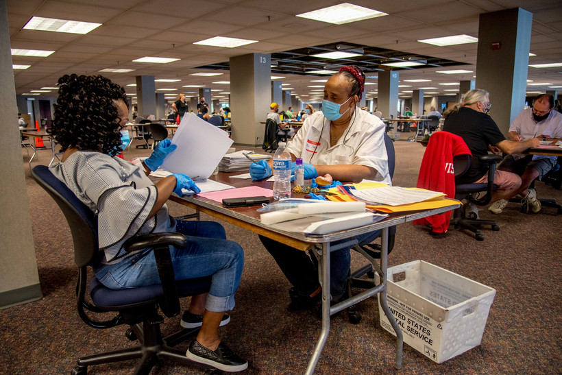 "Election workers process absentee ballots at Milwaukee's ""central count"" facility"