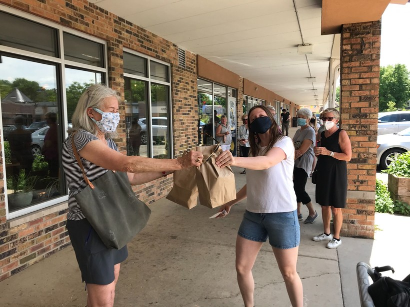 Allyson Deets from Manna Cafe hands takeout food to customer Paula Kraemer in this June 19, 2020 photo.