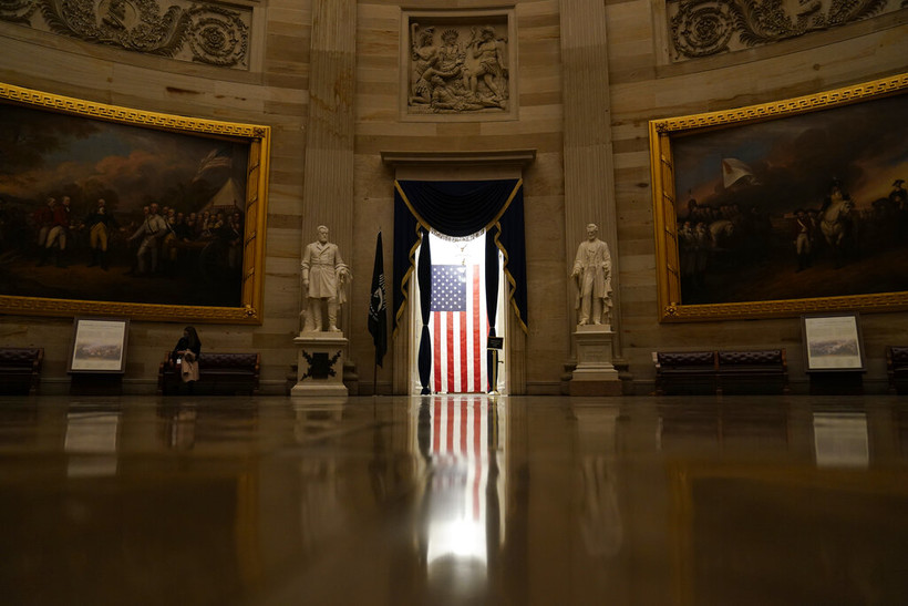 Light shines on an American flag as seen from the Capitol Rotunda in Washington, Wednesday, Jan. 13, 2021