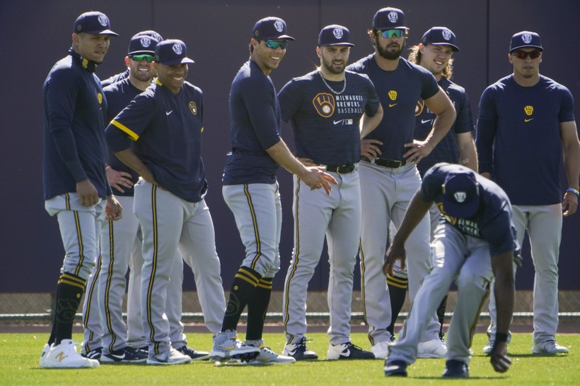 Milwaukee Brewers teammates watch as Lorenzo Cain fields a ball during practice