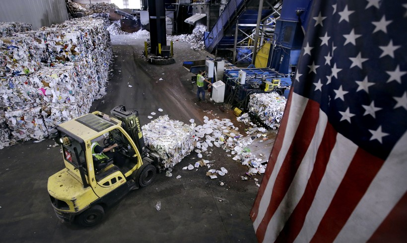 A forklift carries a bundle of recycled materials