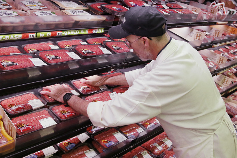 A grocer stocks meat during the coronavirus pandemic
