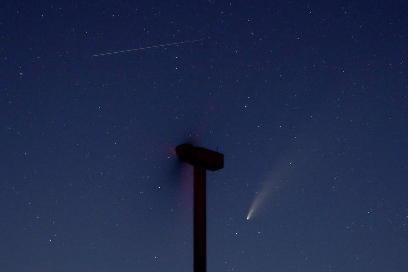 The comet Neowise, below, is seen in the night sky beyond a wind turbine