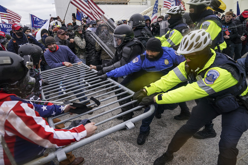 photo rioters try to break through a police barrier at the Capitol in Washington