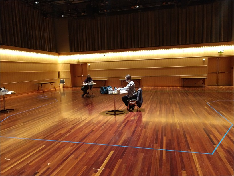 an actor sits at a table in a mostly empty room