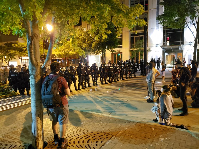 Police face off against protesters in downtown Madison on Sunday night.