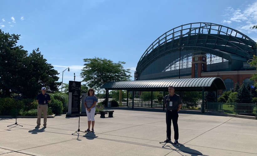 Game day workers speak to reporters outside Miller Park