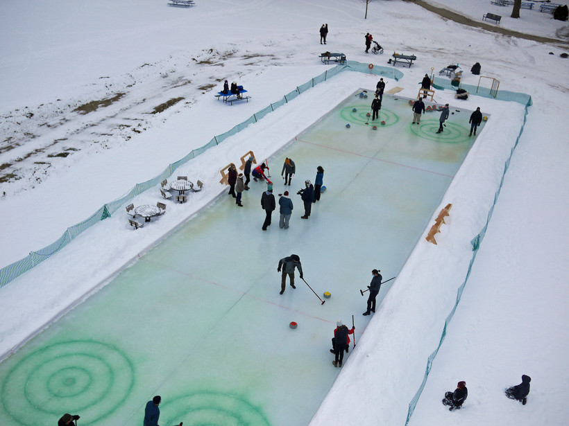 Curlers practice skills on a built-in sheet of ice at a park in Monona