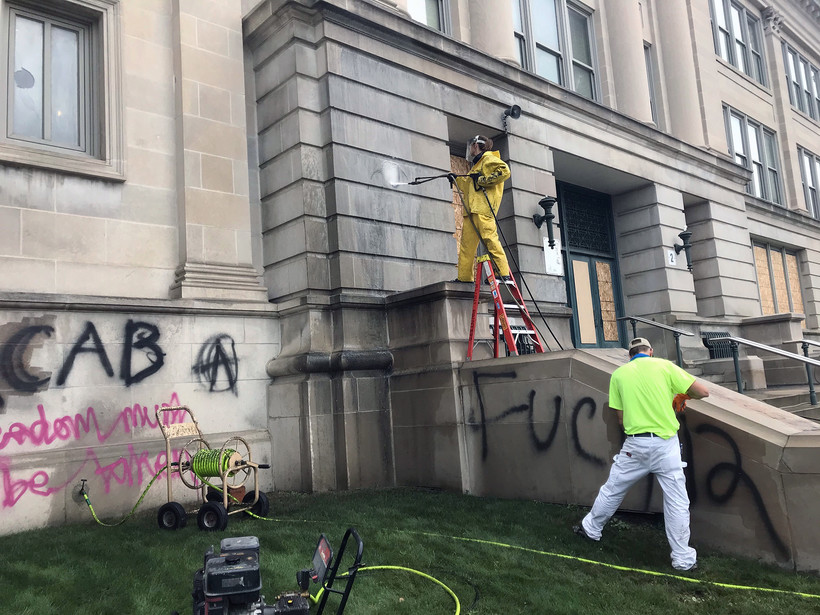 Workers clean off graffiti