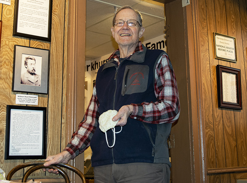 Terry Mesch, volunteer coordinator of the Old Courthouse Museum in Durand, poses next to a framed picture of William Boyd Newcomb