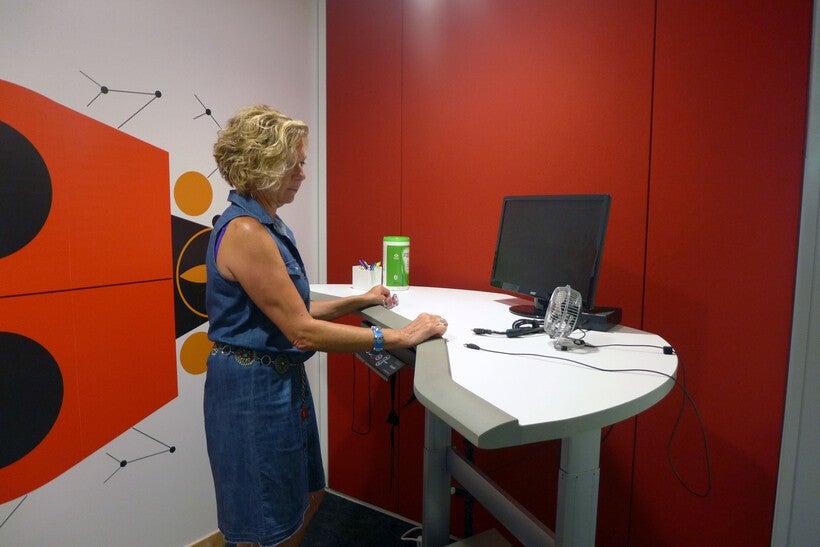 Mindy MacWilliams stands at a treadmill desk