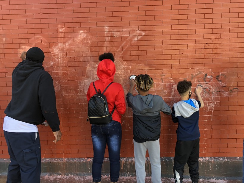 family works to clean up graffiti