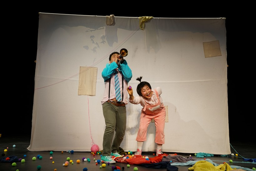 Two actors on stage with props