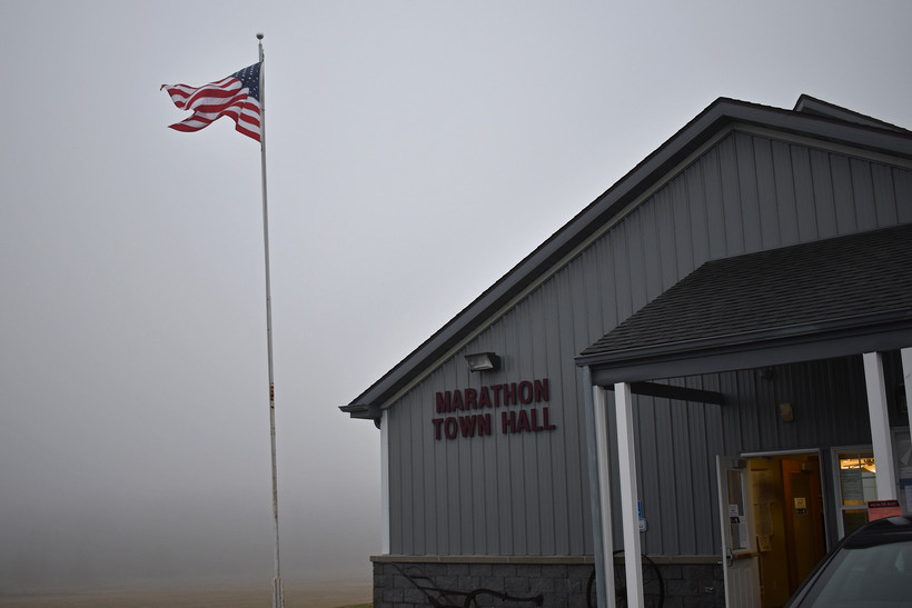 An American flag is visible in the fog outside the Marathon City Town Hall