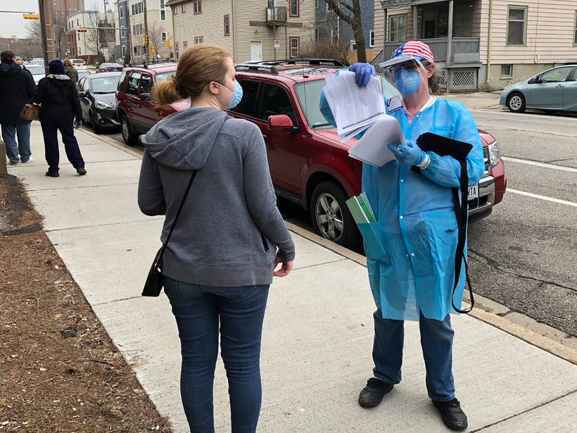 Caroline Hildebrand talksto a poll worker with the Wisconsin National Guard