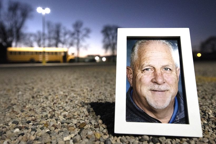 A school bus can be seen behind a framed photo of Duane Bark