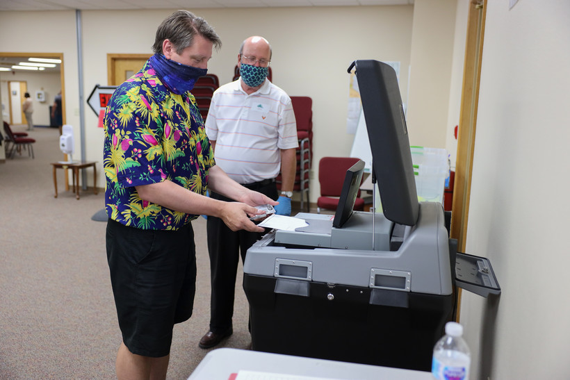 Kevin Mineau inserts his ballot into the DS200 vote-counting machine during the partisan primary