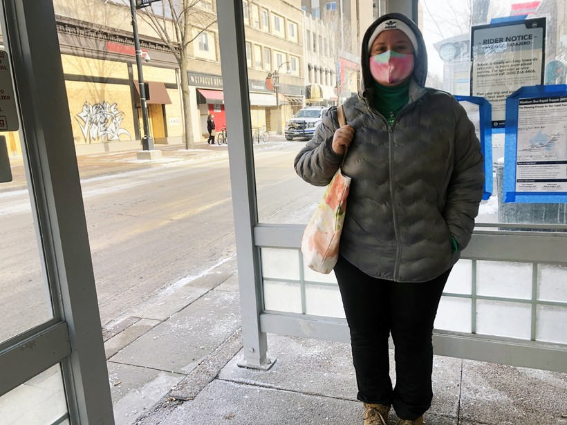 A woman with a face mask stands at a bus stop