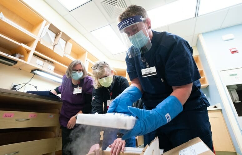 UW Health pharmacy technicians unpack a box of Pfizer's COVID-19 vaccine